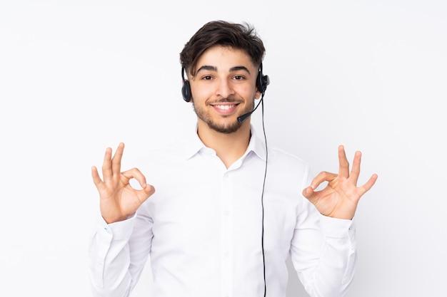 Telemarketer hombre árabe que trabaja con un auricular en la pared blanca que muestra un signo bien con los dedos