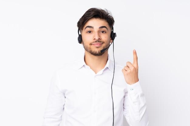 Telemarketer hombre árabe que trabaja con un auricular en la pared blanca señalando con el dedo índice una gran idea