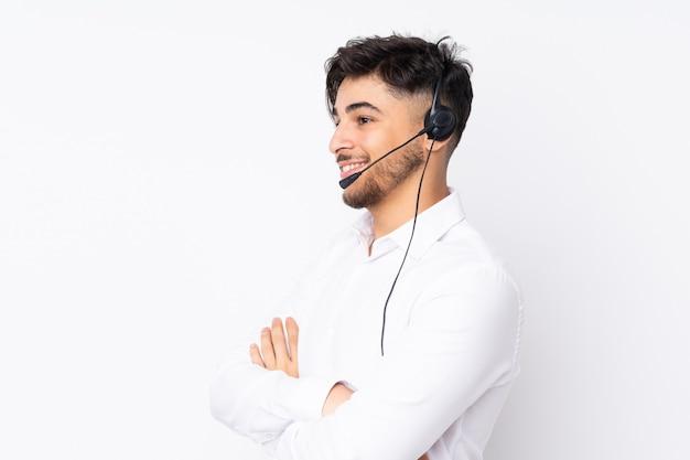 Telemarketer hombre árabe que trabaja con un auricular en la pared blanca