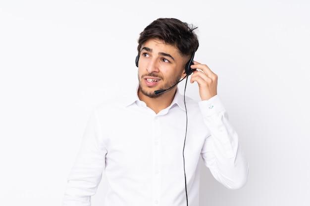 Telemarketer hombre árabe trabajando con un auricular en la pared blanca escuchando algo