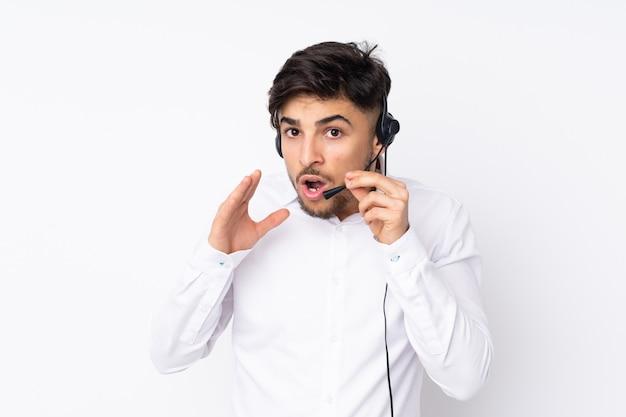 Telemarketer hombre árabe trabajando con un auricular en la pared blanca susurrando algo