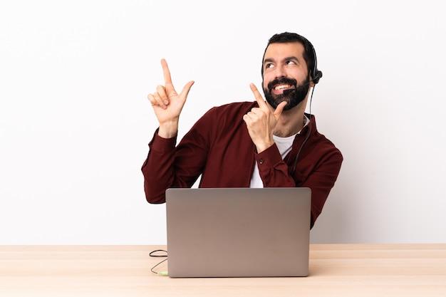 Telemarketer hombre caucásico que trabaja con un audífono y un portátil apuntando con el dedo índice una gran idea