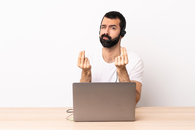 Telemarketer hombre caucásico que trabaja con un auricular y una computadora portátil haciendo dinero gesto pero está arruinado