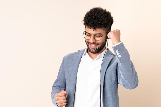 Telemarketer hombre marroquí que trabaja con un auricular aislado en la pared beige celebrando una victoria