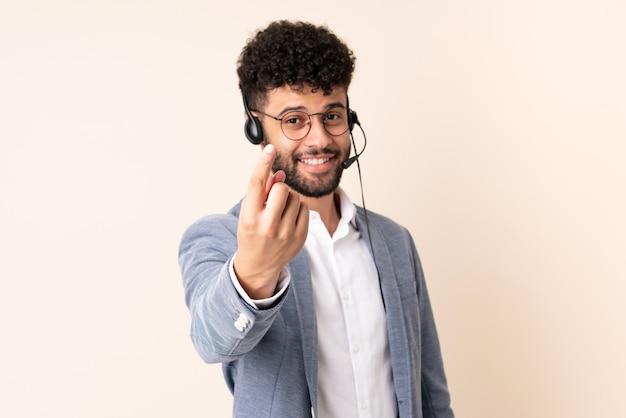 Telemarketer hombre marroquí que trabaja con un auricular aislado en la pared beige haciendo gesto que viene