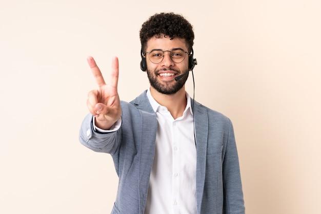 Telemarketer hombre marroquí que trabaja con un auricular aislado en la pared beige sonriendo y mostrando el signo de la victoria