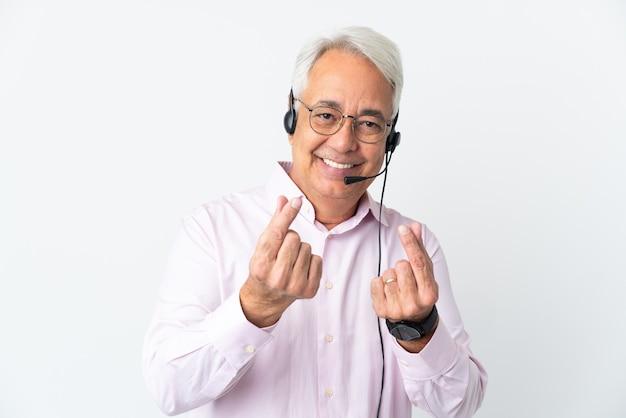 Telemarketer hombre de mediana edad que trabaja con un auricular aislado haciendo gesto de dinero