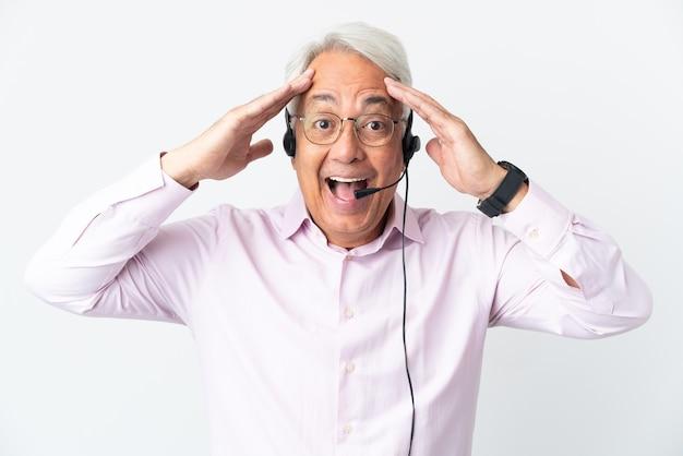 Telemarketer hombre de mediana edad que trabaja con un auricular aislado en la pared blanca con expresión de sorpresa