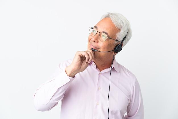 Telemarketer hombre de mediana edad que trabaja con un auricular aislado en la pared blanca y mirando hacia arriba