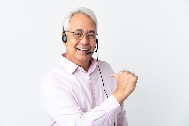 Telemarketer hombre de mediana edad que trabaja con un auricular aislado en la pared blanca orgulloso y satisfecho de sí mismo
