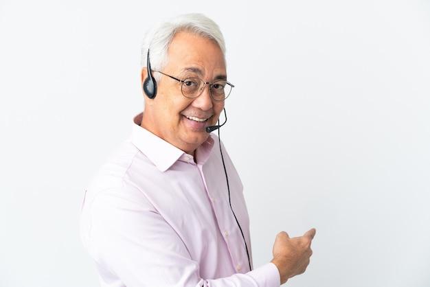 Telemarketer hombre de mediana edad que trabaja con un auricular aislado sobre fondo blanco apuntando hacia atrás