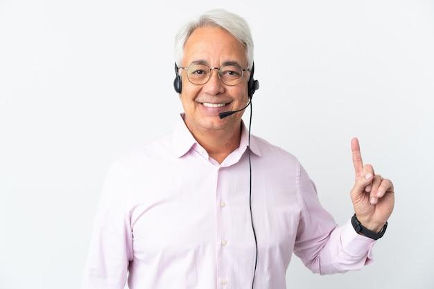 Telemarketer hombre de mediana edad que trabaja con un auricular aislado sobre fondo blanco apuntando hacia una gran idea