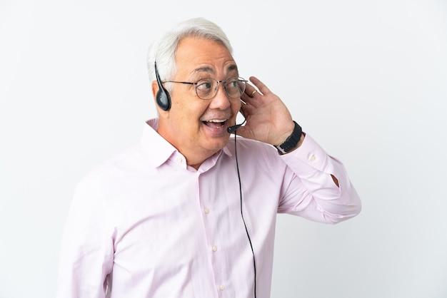 Telemarketer hombre de mediana edad que trabaja con un auricular aislado sobre fondo blanco escuchando algo poniendo la mano en la oreja