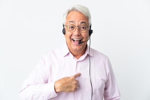 Telemarketer hombre de mediana edad que trabaja con un auricular aislado sobre fondo blanco con expresión facial sorpresa