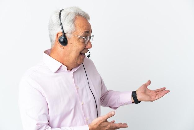 Telemarketer hombre de mediana edad que trabaja con un auricular aislado sobre fondo blanco con expresión de sorpresa mientras mira de lado