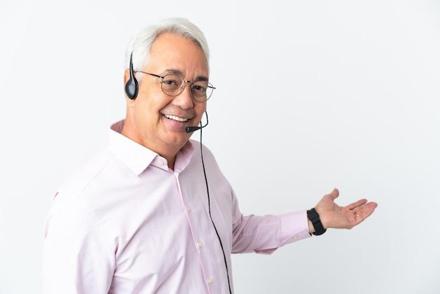 Telemarketer hombre de mediana edad que trabaja con un auricular aislado sobre fondo blanco extendiendo las manos hacia el lado para invitar a venir