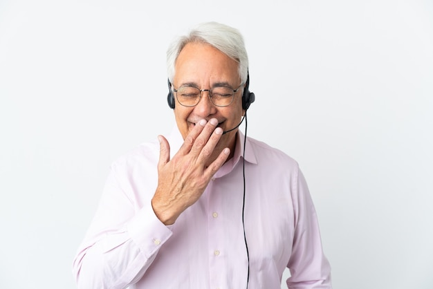 Telemarketer hombre de mediana edad que trabaja con un auricular aislado sobre fondo blanco feliz y sonriente cubriendo la boca con la mano
