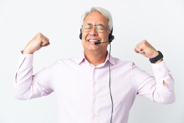 Telemarketer hombre de mediana edad que trabaja con un auricular aislado sobre fondo blanco haciendo un gesto fuerte
