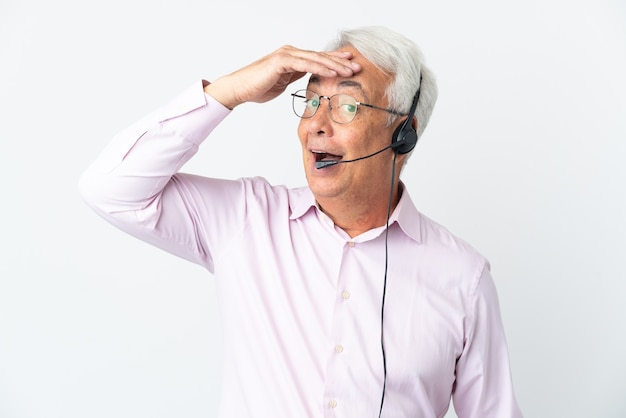 Telemarketer hombre de mediana edad que trabaja con un auricular aislado sobre fondo blanco haciendo gesto de sorpresa mientras mira hacia el lado