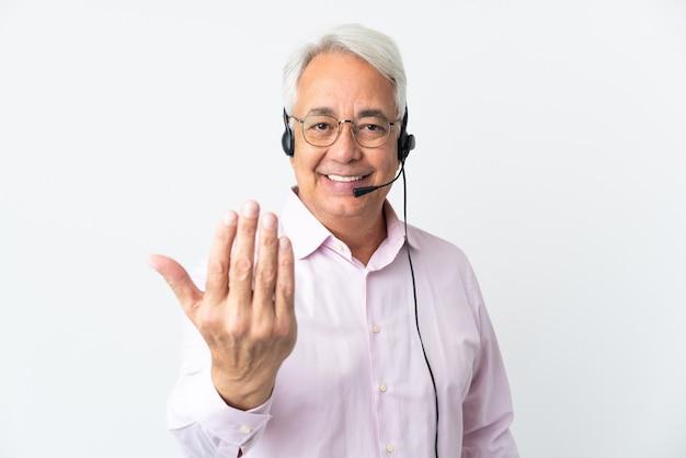 Telemarketer hombre de mediana edad que trabaja con un auricular aislado sobre fondo blanco invitando a venir con la mano. feliz de que hayas venido