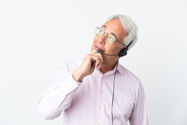 Telemarketer hombre de mediana edad que trabaja con un auricular aislado sobre fondo blanco mirando hacia arriba mientras sonríe