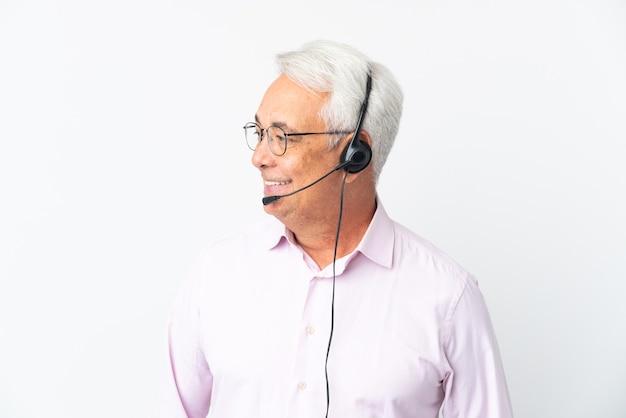 Telemarketer hombre de mediana edad que trabaja con un auricular aislado sobre fondo blanco mirando de lado