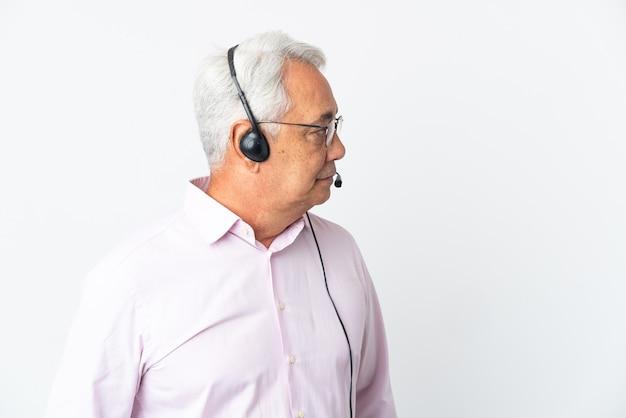 Telemarketer hombre de mediana edad que trabaja con un auricular aislado sobre fondo blanco mirando hacia el lado