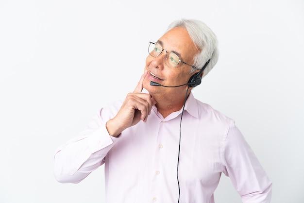 Telemarketer hombre de mediana edad que trabaja con un auricular aislado sobre fondo blanco pensando en una idea mientras mira hacia arriba