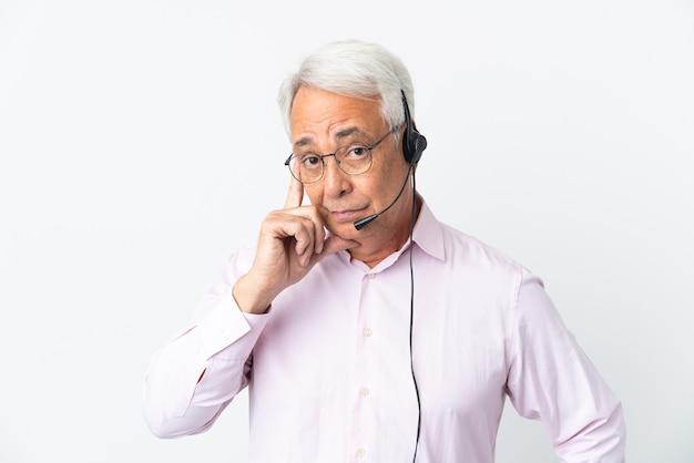 Telemarketer hombre de mediana edad que trabaja con un auricular aislado sobre fondo blanco pensando en una idea