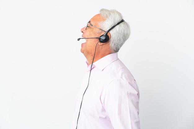 Telemarketer hombre de mediana edad que trabaja con un auricular aislado sobre fondo blanco riendo en posición lateral
