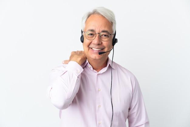 Telemarketer hombre de mediana edad que trabaja con un auricular aislado sobre fondo blanco riendo