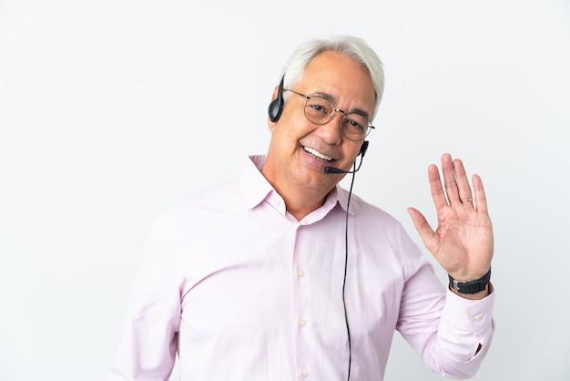Telemarketer hombre de mediana edad que trabaja con un auricular aislado sobre fondo blanco saludando con la mano con expresión feliz