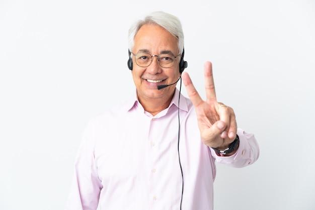 Telemarketer hombre de mediana edad que trabaja con un auricular aislado sobre fondo blanco sonriendo y mostrando el signo de la victoria