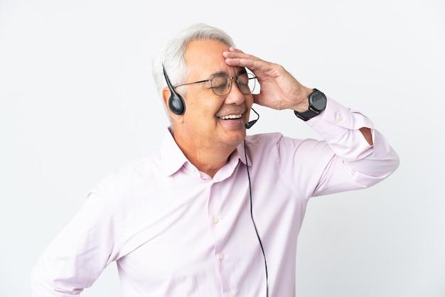 Telemarketer hombre de mediana edad que trabaja con un auricular aislado sobre fondo blanco sonriendo mucho