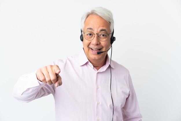 Telemarketer hombre de mediana edad que trabaja con un auricular aislado sobre fondo blanco sorprendido y apuntando hacia delante