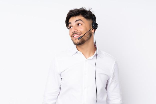 Telemarketer hombre trabajando con un auricular aislado en la pared blanca riendo y mirando hacia arriba
