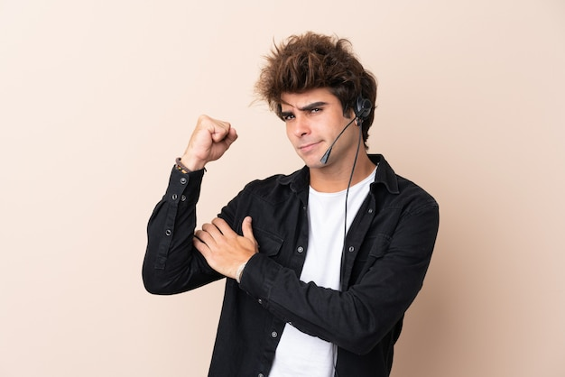 Telemarketer hombre trabajando con un auricular sobre pared aislada haciendo un gesto fuerte