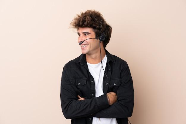Telemarketer hombre trabajando con un auricular sobre pared aislada riendo