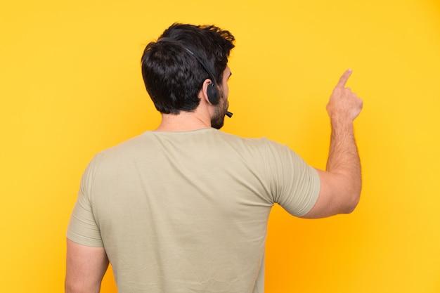 Telemarketer hombre trabajando con un auricular sobre pared amarilla aislada apuntando hacia atrás con el dedo índice