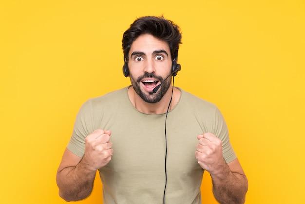 Telemarketer hombre trabajando con un auricular sobre pared amarilla aislada celebrando una victoria