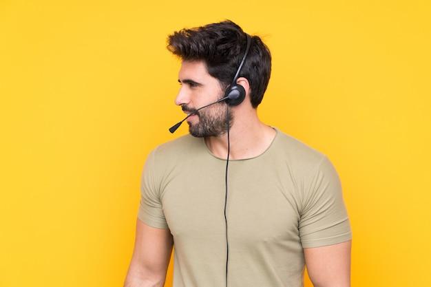 Telemarketer hombre trabajando con un auricular sobre pared amarilla aislada mirando hacia el lado