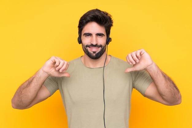 Telemarketer hombre trabajando con un auricular sobre pared amarilla aislada orgulloso y satisfecho de sí mismo