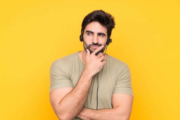 Telemarketer hombre trabajando con un auricular sobre pared amarilla aislada pensando en una idea