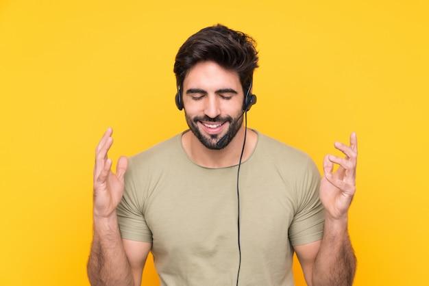 Telemarketer hombre trabajando con un auricular sobre pared amarilla aislada riendo