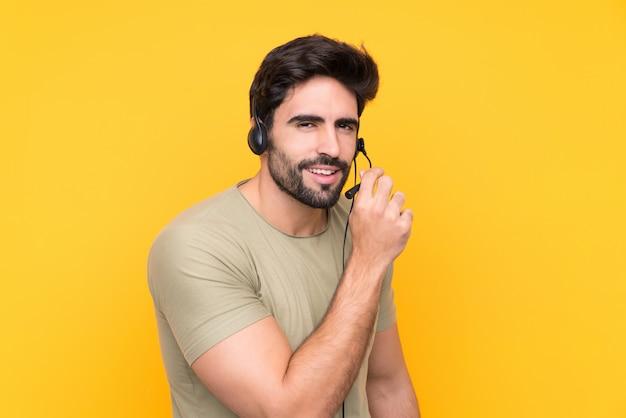 Telemarketer hombre trabajando con un auricular sobre pared amarilla aislada susurrando algo