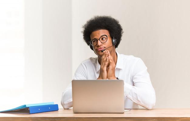 Telemarketer joven hombre negro ideando un plan