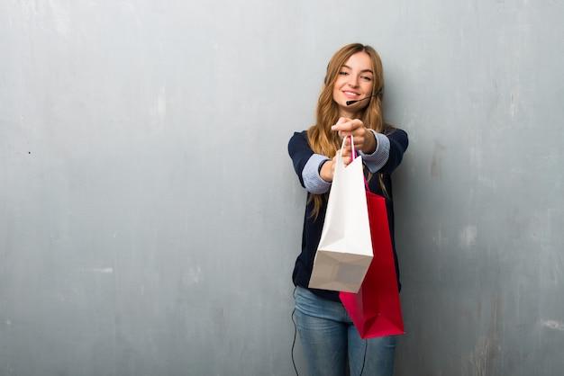 Telemarketer mujer sosteniendo un montón de bolsas de compras