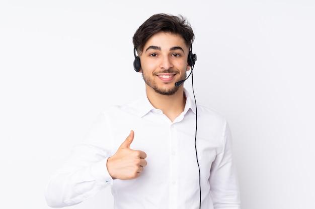 Telemarketer trabajando con un auricular aislado en la pared blanca dando un gesto de aprobación