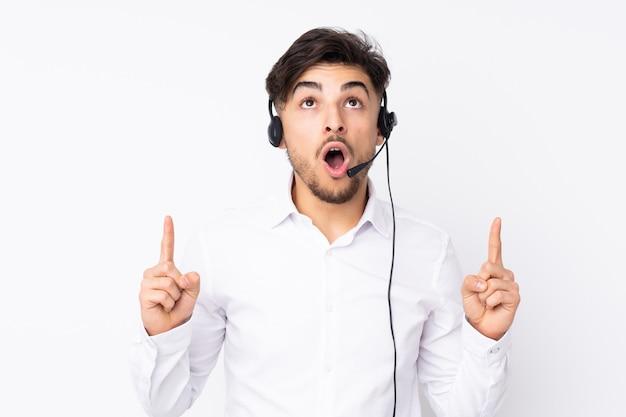 Telemarketer trabajando con un auricular aislado en la pared blanca señalando con el dedo índice una gran idea