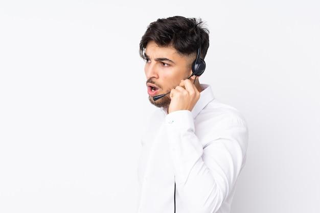 Telemarketer trabajando con un auricular aislado en la pared blanca